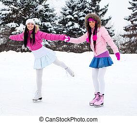 two girls ice skating - two beautiful girls wearing warm...