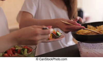 Two girls impose an omelet and vegetable salad in a plate, close-up.