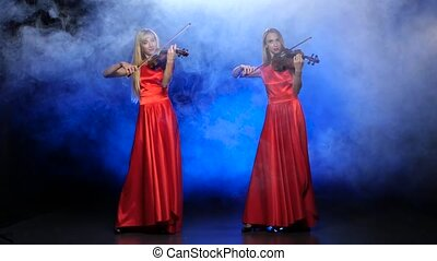 Two girls in a red dress playing the violin. Studio. Smoke