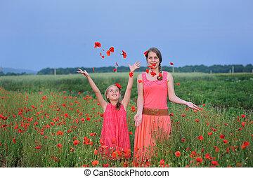 two girls in a red dress walking on the poppy field in Spring