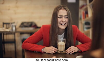 Two girls in cafe laughing and talking.