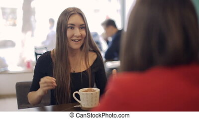 Two girls in  cafe smiling and talking