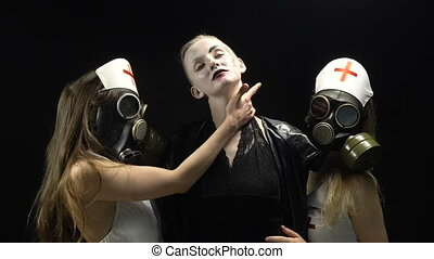 Two girls in gas mask with woman in black