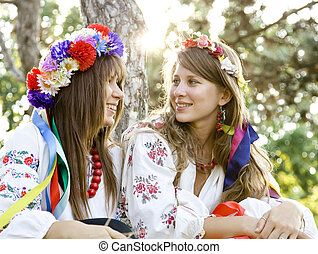 Two girls in national slavic costumes at outdoor.