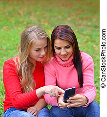 Two girls in park with a mobile phone