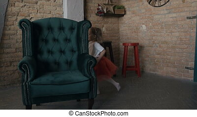 Two girls in red skirts running one after another around a green chair that stands in the living room near the Christmas tree