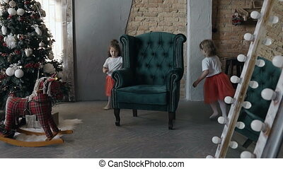 Two girls in red skirts running one after another around a green chair that stands in the living room near the Christmas tree. Happy twin kids