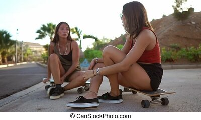 Two girls in skate Park sit on boards and talk smiling and...