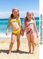 Two girls in swimwear on beach. - Full length Portrait of...