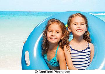 Two girls in swimwear with big blue rubber ring
