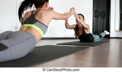 Two girls in the gym in sportswear while being each other's friends perform the exercise of superman in a dynamic swinging on his stomach. Exercise to strengthen the muscles of the press and back. Pilates