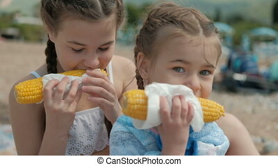 Two girls in the summer eat boiled corn in a napkin.