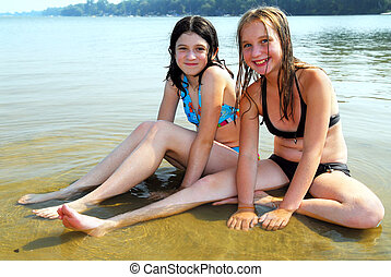 Two girls in water - Two preteen girls sitting in shallow ...