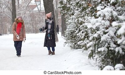 Two girls in winter walking and talking with each other. Hugging