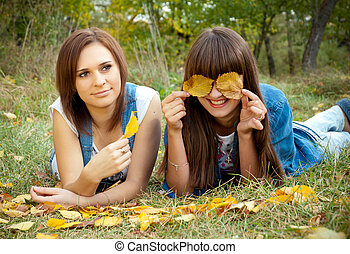 Two girls joking with yellow leaves