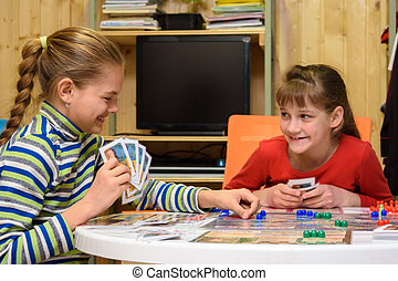 Two girls joyfully laugh while playing board games at the table