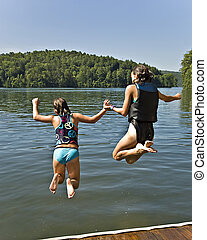 Two Girls Jumping into Lake - Two girls holding hands and...