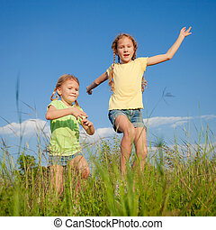 Two Girls jumping on the road