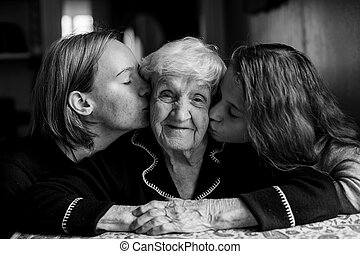 Two girls kiss their grandmother. Black and white portrait.