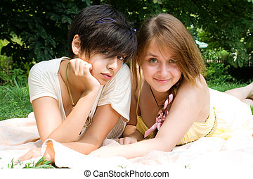 Two girls laying on the coverlet upon green grass