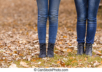 Two girls legs in boots on autumn leaves