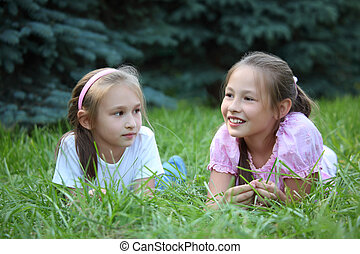 Two girls lie on grass in summer