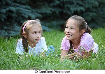 Two girls lie on grass in summer