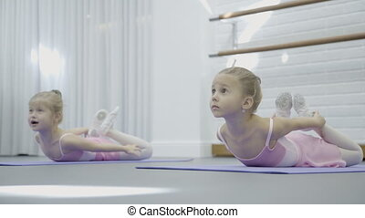 Two girls lie on mats and perform stretching for development of spine.