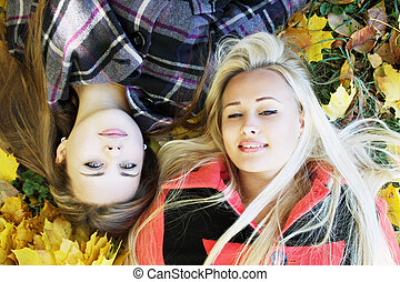 two girls lie on the grass