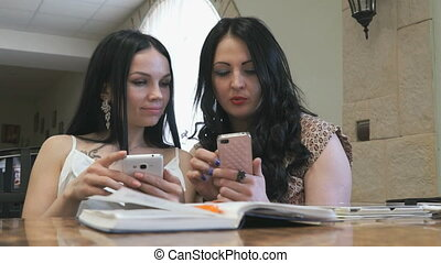 Two girls look at pictures on mobile phone in cafe