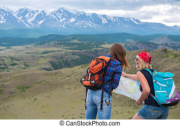 Two girls look at the map on the background of mountains and thi