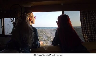 two girls look out the window of the autotrailer to the seashore