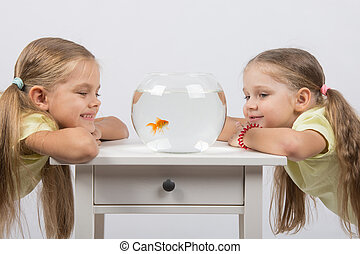 Two girls looking at a goldfish in a small fishbowl