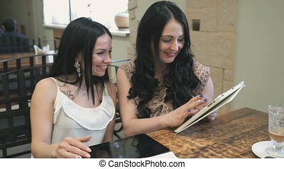 Two girls looking at pictures on electronic tablet