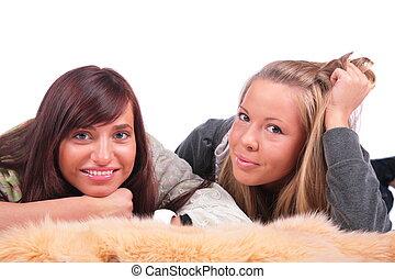 Two girls lying in fur