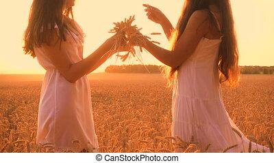 Two girls make a wreath of ears on wheat field - Two girls...