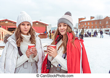 Two girls make friends in winter pose. In hands of cups coffee tea, snack breakfast on nature in New Year holidays and vacations. Keep warm on a hot drink. Emotions of joy, smiles and fun at resort.