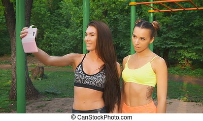 Two girls make merry fitness selfie. Sports figures and good...