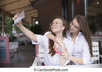 two girls makeing a selfie in summer cafe