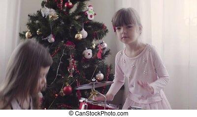 Two girls near christmas tree playing drum kit