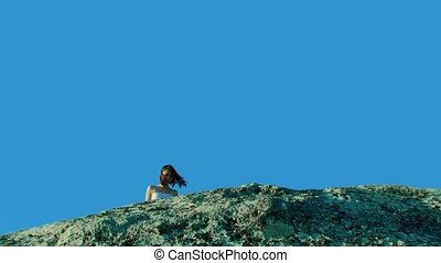 Two girls on a rock against the blue sky.