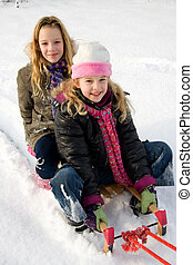 Two girls on a sled