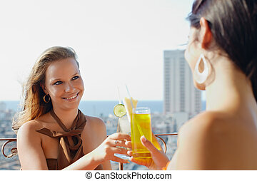 two girls on holidays in Cuba, toasting with cocktails