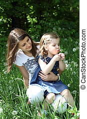 Two girls on the glade with dandelions