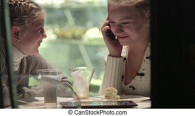 Two girls on the phone in window of coffee shop at night