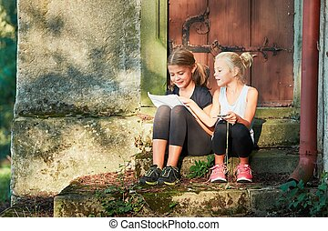 Two girls on the trip sit on the church stairs and look...