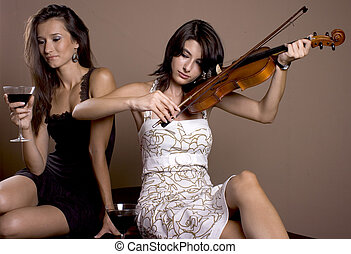 two girls - one girl drinking wine and one playing at a...