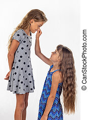 Two girls, one stood on a chair and the other holds the first by the nose