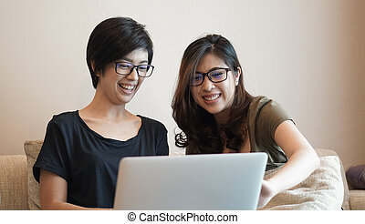 Two women friends partner on e-commerce business working from home through computer together