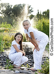 Two girls play at a fountain